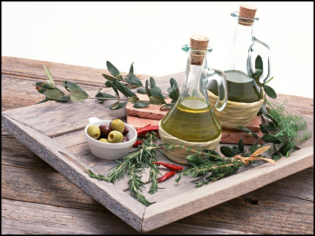 olives, olive oil, chilis, rosemary and thyme on a wooden tray and table