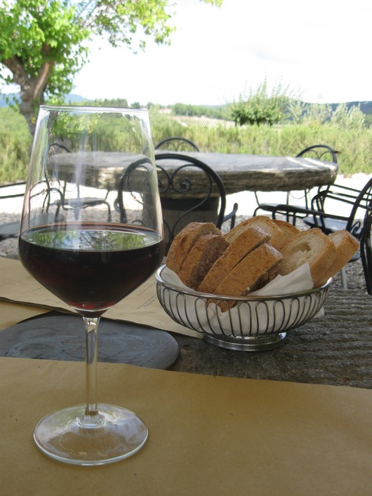 a glass of wine and some bread on an outside restaurant table in Italy