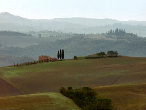 Quintessential Tuscany hills, cypress trees and a stone farmhouse